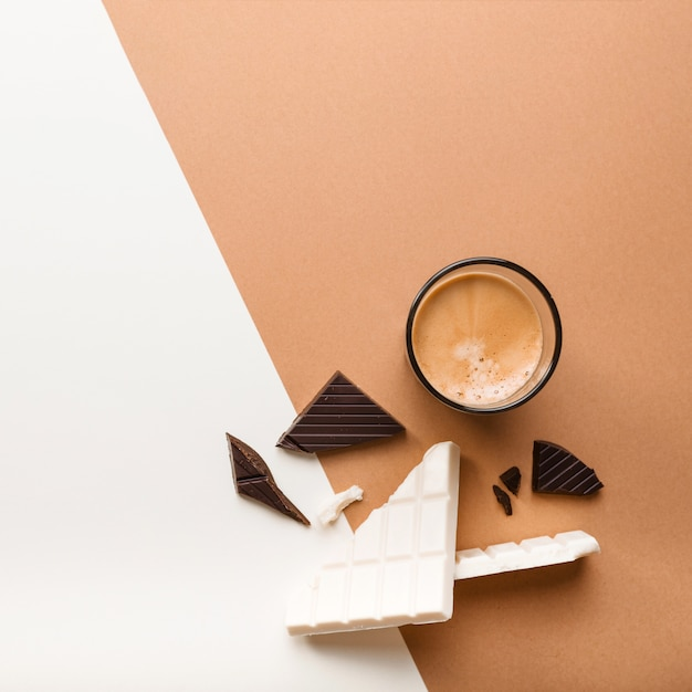 Dark and white chocolate bar with coffee glass on dual backdrop Free Photo