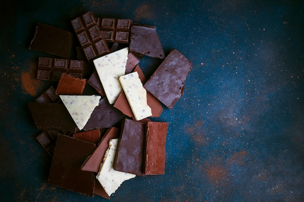 Dark, white and milk chocolate pieces. top view Free Photo