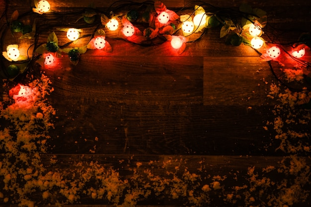 Dark wood wall with lights and snow Free Photo