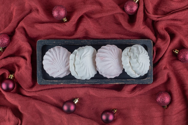 Una tavola di legno scuro con vaniglia e zefiri rosa con palle di natale. Foto Gratuite