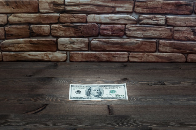 On a dark wooden table near a brick wall of a bill one hundred dollars lit by a ray of light. Premium Photo