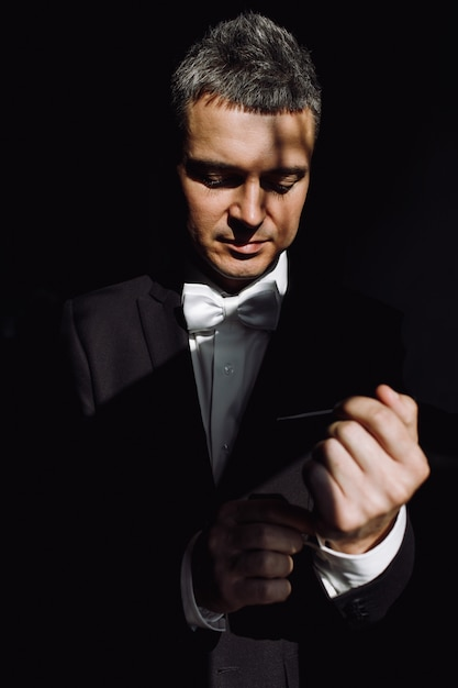 Darkness hides handsome groom while he fixes his jacket Free Photo