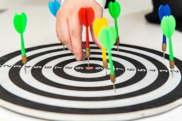 Dart arrow in hand on target dartboard, goal and target setting in business concept. Premium Photo