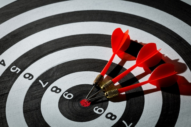 Dart arrow hitting in the target center of dartboard. concept of the success Premium Photo