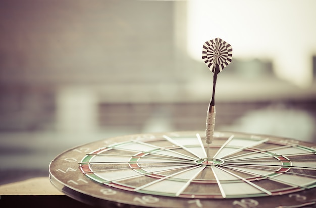 Dart arrow hitting in the target center of dartboard with modern city and sunset background. Premium Photo