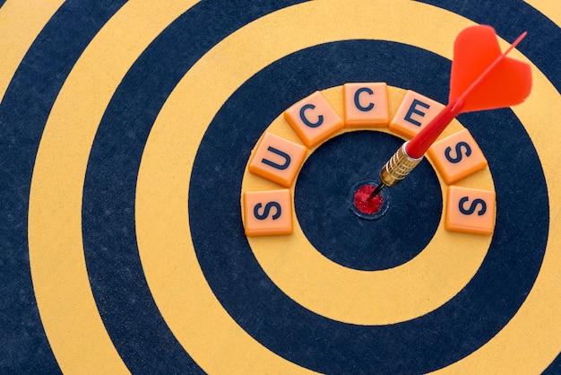 Dart hitting the bullseye target with word success on dartboard Free Photo