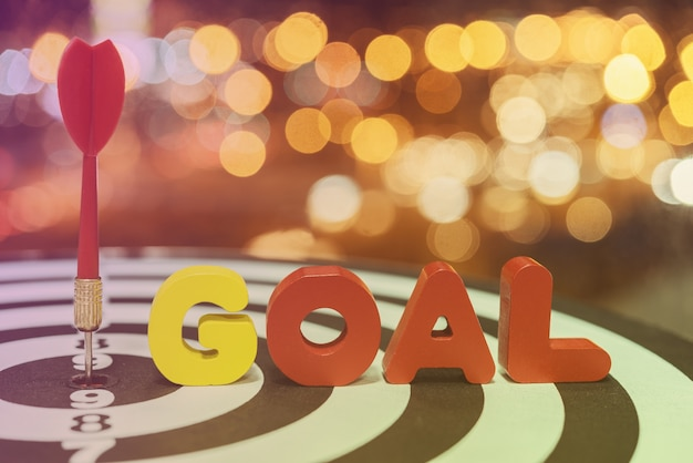 Dart target arrow on bullseye with goal words over bokeh backgro Free Photo