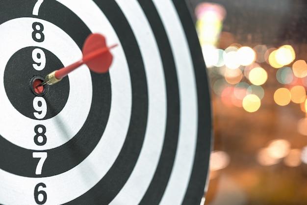 Dart target arrow hitting on bullseye with bokeh background Free Photo