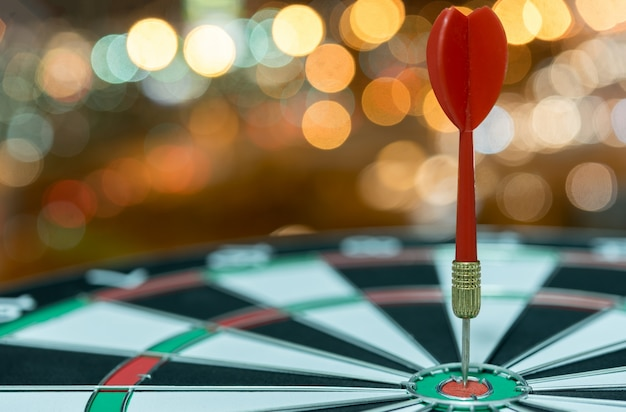 Dart target arrow on bullseye over bokeh background Free Photo