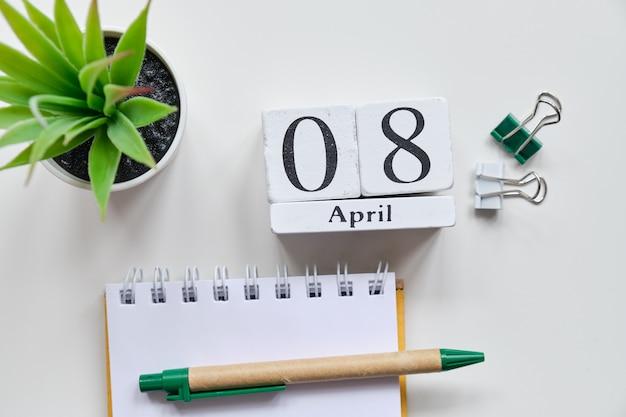 Дата на белых деревянных кубиках - восьмое, 8 апреля на белом столе. вид сверху. Premium Фотографии