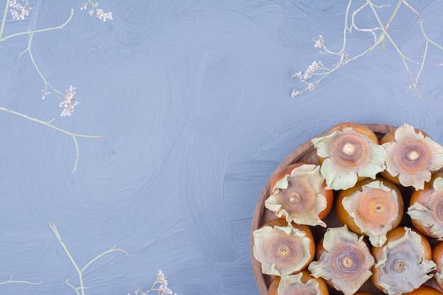 Финиковые сливы в деревянном блюде на синем фоне Бесплатные Фотографии