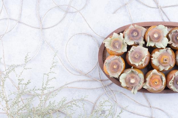 Финиковые сливы в деревянном блюде на сером фоне Бесплатные Фотографии