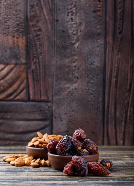 Финики и миндаль в глиняных табличках на фоне деревянных и каменных плиток. вид сбоку. Бесплатные Фотографии