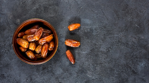 Dates fruit in bowl on black table Free Photo