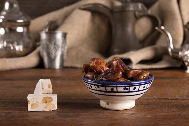 Dates fruit in bowl with turkish delight on table Free Photo