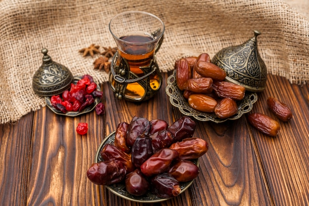 Dates fruit on plate with glass of tea on table Free Photo