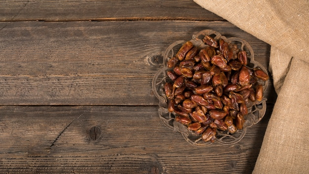 Dates fruit on plate on wooden table Free Photo