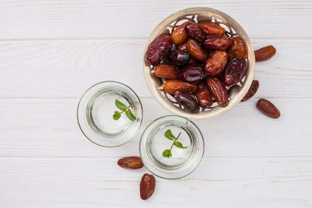 Dates fruit on small plate with water in bowls Free Photo