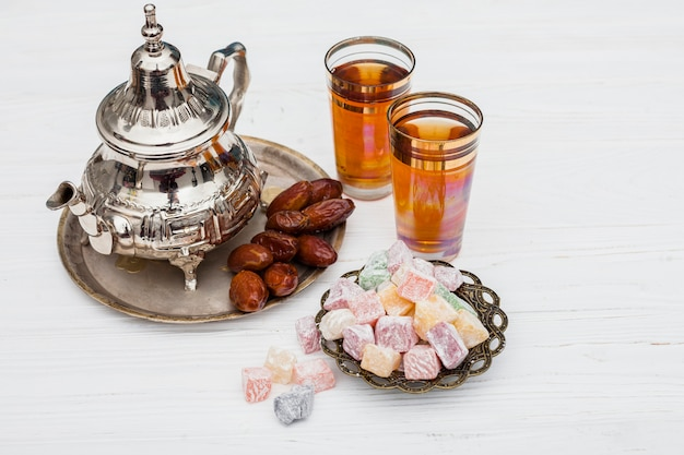 Dates fruit with turkish delight and teapot Free Photo