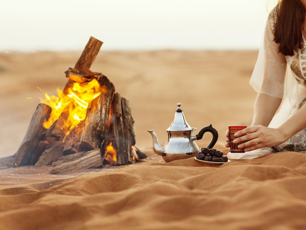 Dates, teapot, cup with tea near the fire in the desert with a beautiful background Premium Photo