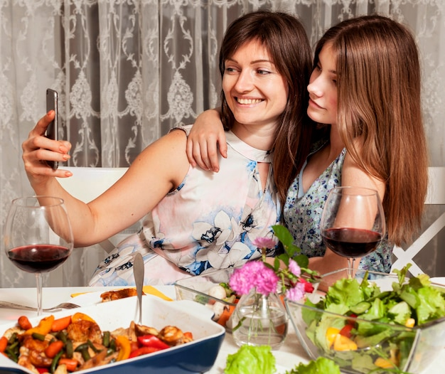 Дочь и мать, принимая селфи за обеденным столом Бесплатные Фотографии