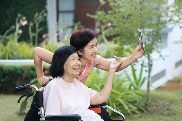 Daughter caring for the elderly asian woman ,do selfie, happy, smiles in backyard. Premium Photo