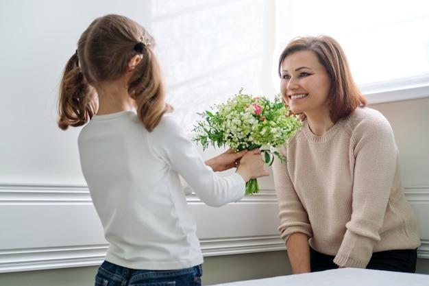 母の日に美しい春の花でお母さんを祝う娘 Premium写真