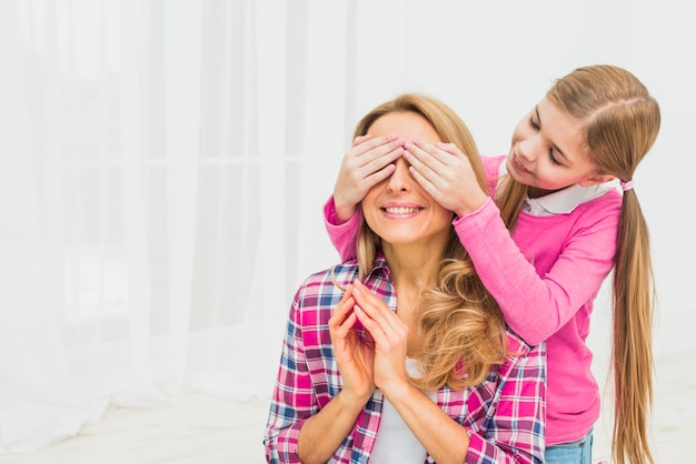 Daughter covering eyes of mother Free Photo