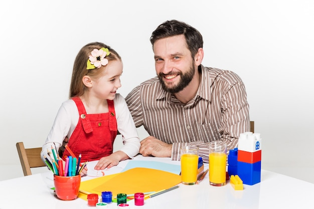 Daughter and father drawing together Free Photo