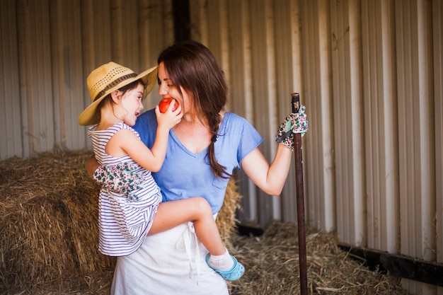 Daughter feeding red apple to her mother standing in the barn Free Photo