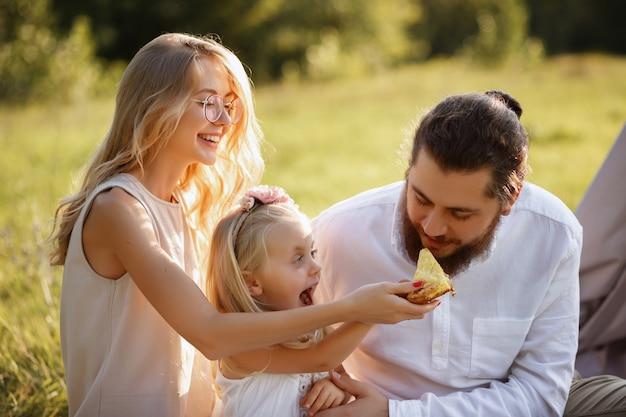 Дочь кормит папиной пирог. счастливая семья на летнем пикнике. размытый фон Premium Фотографии