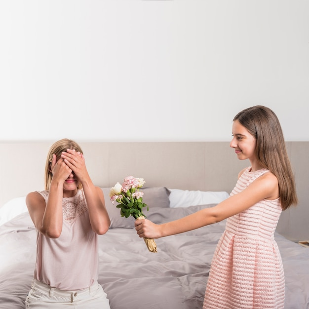Daughter giving flowers bouquet to mother in bedroom Free Photo