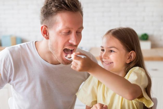 Дочь дает еду отцу Premium Фотографии