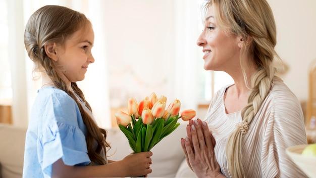 Дочь дарит маме букет тюльпанов в подарок Бесплатные Фотографии
