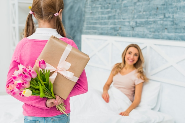 Daughter holding gift and tulips for mother in bed Premium Photo