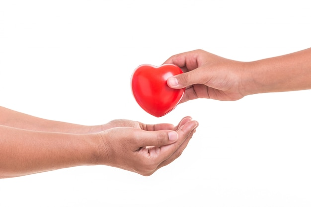 Daughter holding and giving red heart to her mother hand isolated on white Premium Photo