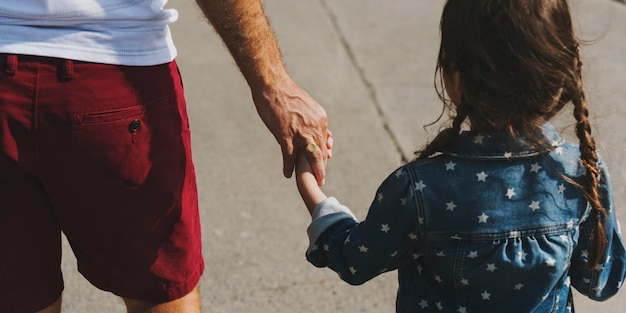 Daughter holding her dad's hand while walking Premium Photo