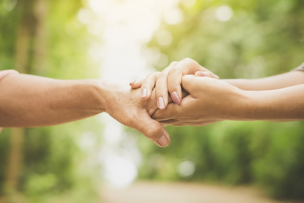 Daughter holding her mother's hand close up Premium Photo