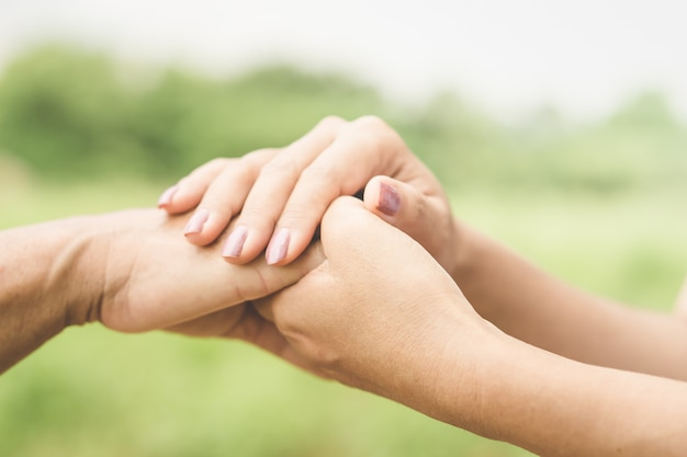 Daughter holding her mother's hand Premium Photo
