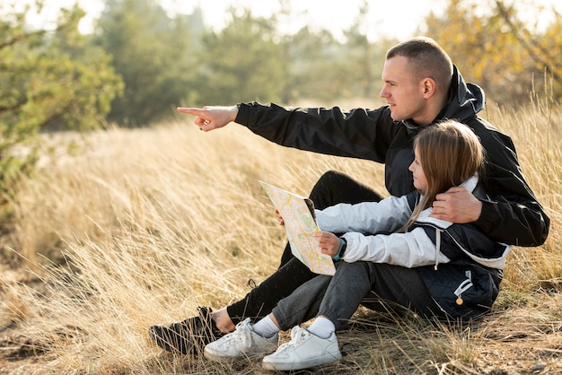 Daughter holding a map and father showing the direction Free Photo