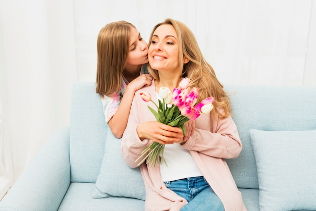 Daughter kissing happy mother with flowers Free Photo