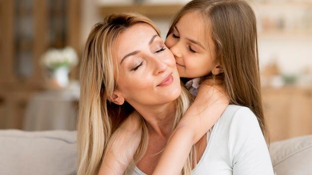 Дочь целует мать дома Premium Фотографии