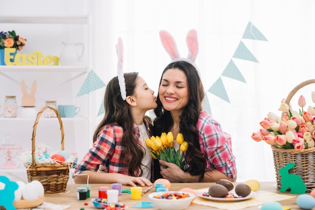 Daughter kissing her mother on easter day celebration Free Photo