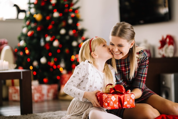 Daughter kissing mother at christmas Free Photo