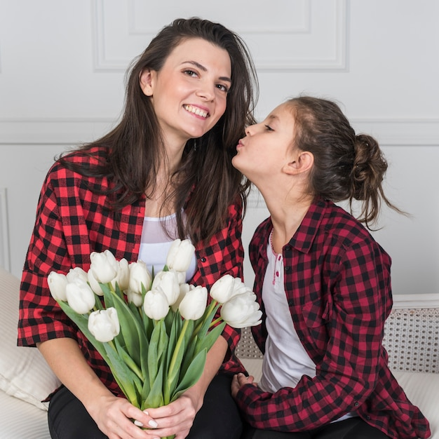 Daughter kissing mother with tulips Free Photo