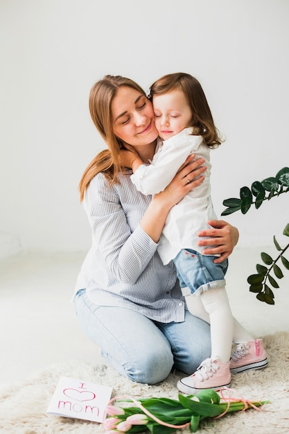 Daughter and mother hugging near greeting card Free Photo