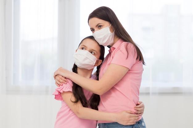 Figlia e madre che indossano maschere mediche Foto Gratuite