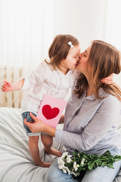 Daughter and mother with greeting card kissing Free Photo
