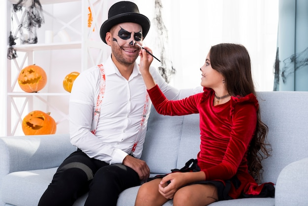 Daughter painting dads face for halloween Free Photo