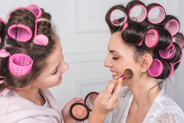 Daughter putting powder on mothers cheek Free Photo